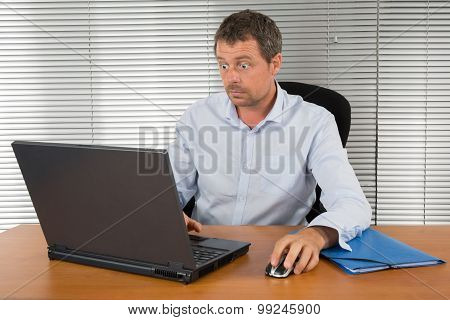 Businessman Stunned And Amazed Staring At His Laptop