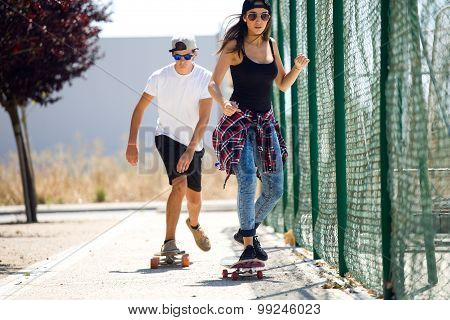 Young Couple Skateboarding In The Street.