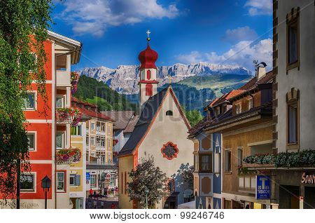 Church on a background of mountains in the resort of Ortisei, Italy