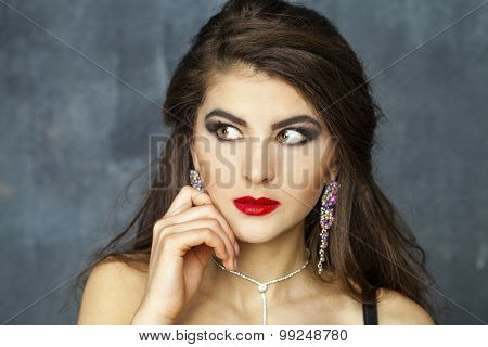 Beautiful Brunette Girl with hairstyle and make up isolated on dark wall background