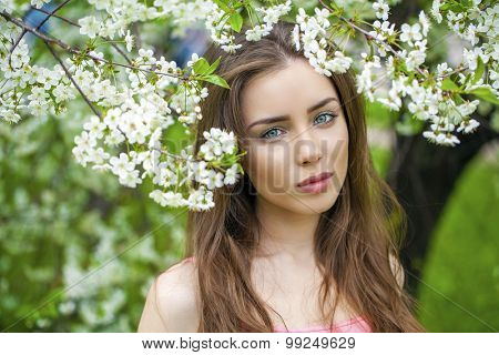 Portrait of beautiful brunette in spring blossom