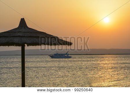 Boat Traveling On Tropical Sea At Sunrise