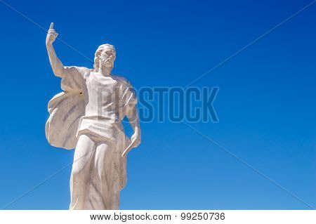 A Statue Of St Elijah The Prophet Holding A Knife On A Blue Sky Background