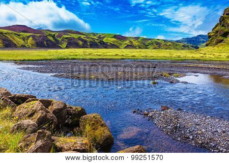 On bottom of canyon many streams flow. Canyon Pakgil in Iceland.  Picturesque basalt hills overgrown green grass and moss