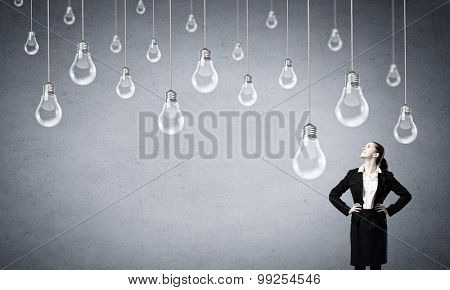 Concept of creativity with woman and light bulbs hanging from above