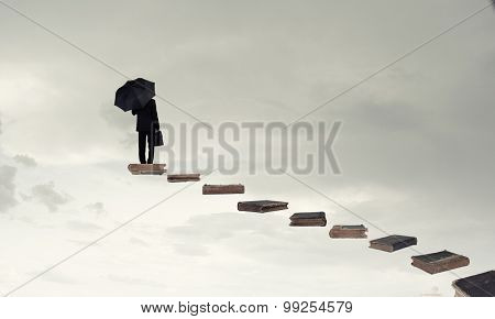 Businessman holding umbrella and waking on career ladder made of books