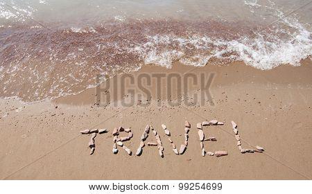 travel written on sandy beach near sea