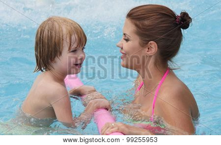 small child learns to swim in the pool with his mother