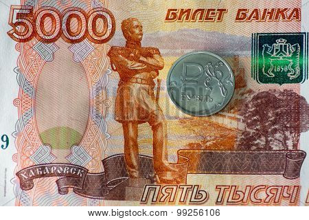 one ruble coin and five thousand rubles banknote