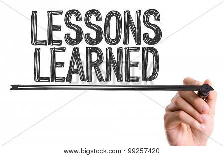 Hand with marker writing the word Lessons Learned