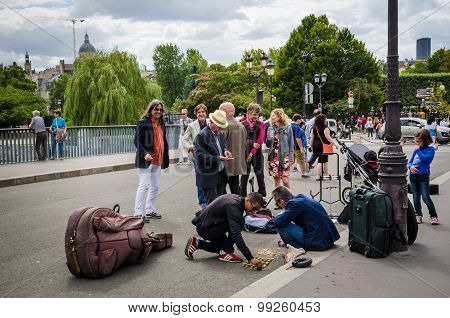 Musicians count their coins on the street after performing on the street in Paris