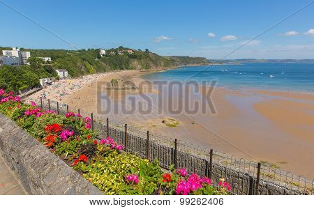 Tenby beach Wales uk in summer with tourists and visitors, blue sea and sky and colourful flowers
