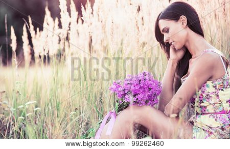 Beautiful girl with summer flowers sitting in a field