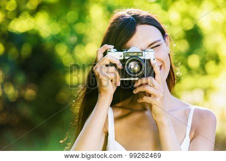 Beautiful smiling girl with old camera on nature