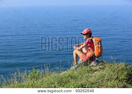 young fitness woman hiker enjoy the view on seaside mountain peak