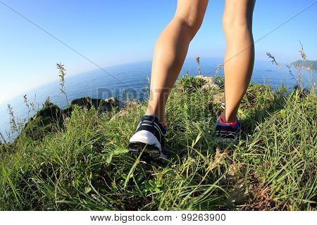 fitness woman runner legs running on seaside mountain grass