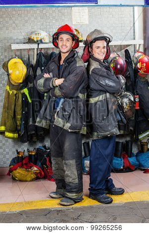 Portrait of smiling young firefighters standing arms crossed at fire station
