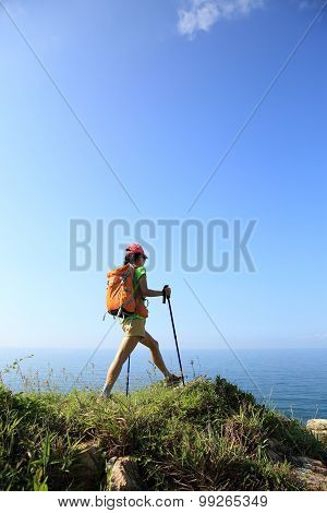 young woman hiker hiking on seaside mountain trail