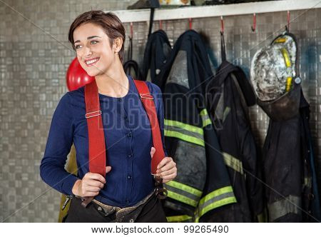 Smiling female firefighter looking away while standing at fire station