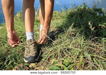 woman hands tying shoelace on seaside mountian grass