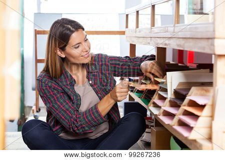 Smiling mid adult female customer choosing paper from shelf in store