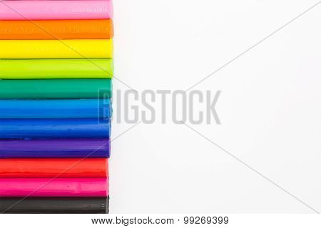 Set of rainbow colors clay sticks on left side of white background