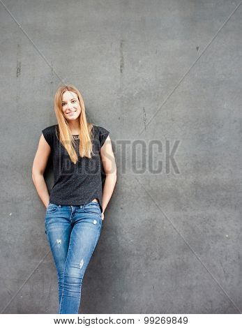 Attractive teenage girl in front of concrete wall