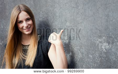 Attractive teenage girl pointing to the side