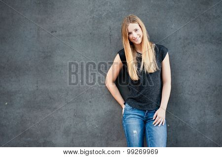 Attractive teenage girl standing in front of concrete wall