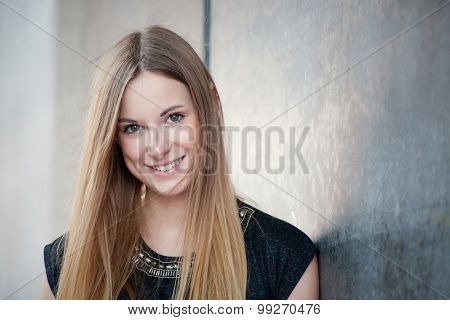 Attractive teenage girl next to concrete wall