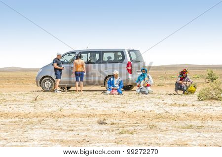 MERZOUGA, MOROCCO, APRIL 13, 2015: Local sellers of souvenirs offer their merchandise to tourists family traveling by car