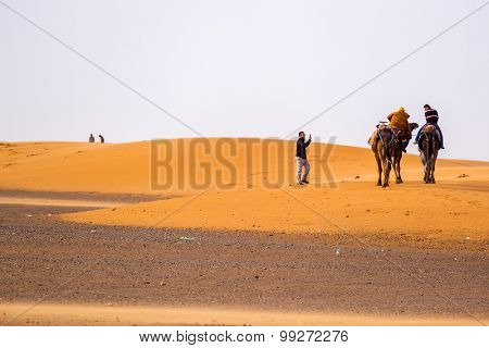 MERZOUGA, MOROCCO, APRIL 13, 2015: Tourist takes photos of people on camels on sand dunes of Erg Chebbi