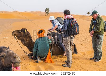 MERZOUGA, MOROCCO, APRIL 13, 2015: Local man in traditional attire helps tourists during a camels ride on sand dunes of Erg Chebbi