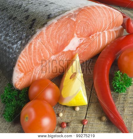 raw salmon, vegetables and spices on an old wooden table