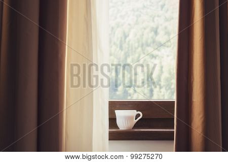 Cup of coffee at the window. Warm tones