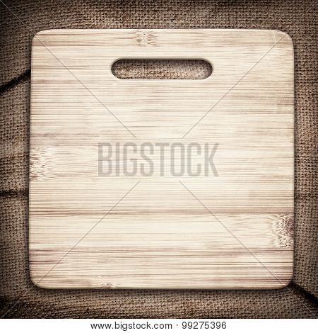 Old cutting board used for cooking on brown crumple burlap tablecloth