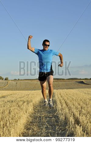 Sport Man Running Outdoors On Straw Field Doing Victory Sign In Frontal Perspective