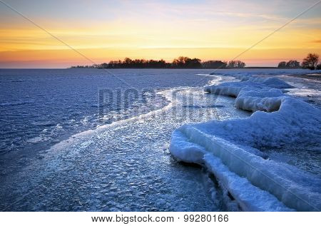 Winter landscape with lake and sunset fiery sky. Composition of nature.