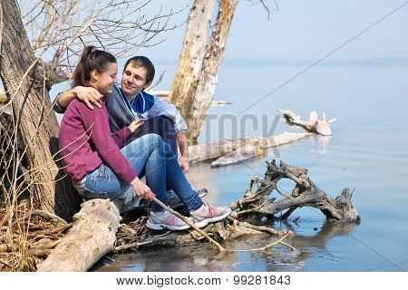 Lovers Sitting On A Snag Ot The Coast And Looking At Each Other. Romantic Scene