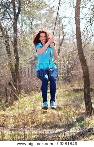 Beautiful Girl Swinging On Bungee In The Forest. Girl Swinging On The Rope