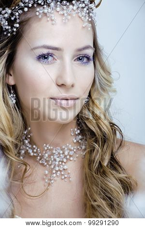 Beautiful young snow queen make up and jewelry ice toned