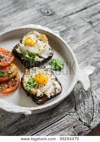 Toast With Feta Cheese And Fried Quail Egg, Fresh Tomatoes On A Light Wooden Surface - A Healthy Bre