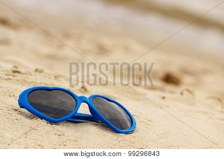 Blue Sunglasses Shaped Heart On The Sand