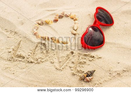 Heart Of Shells And Sunglasses On Sand At The Beach