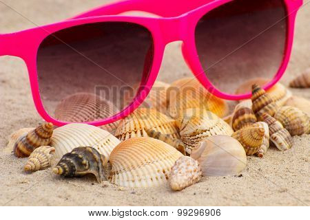 Heap Of Shells And Pink Sunglasses On Sand At The Beach