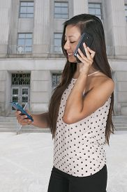 image of juggling  - Beautiful woman talking and multitasking while juggling multiple cell phones and conversations - JPG