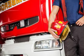 stock photo of firefighter  - Midsection of male firefighter holding red helmet while leaning on firetruck at station - JPG