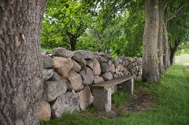 stock photo of old stone fence  - An old dry stone wall with old trees and a bench - JPG