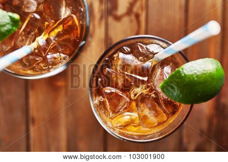 iced tea with lime wedge with retro paper straw shot top down