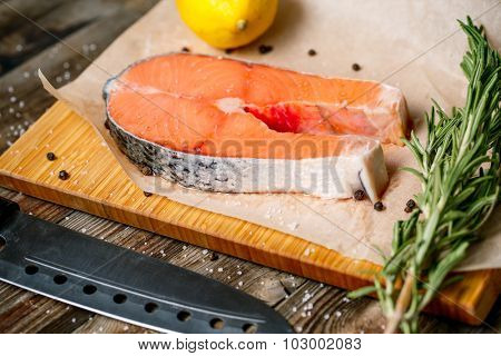 close up fresh steak salmon with knife on wooden cutting board